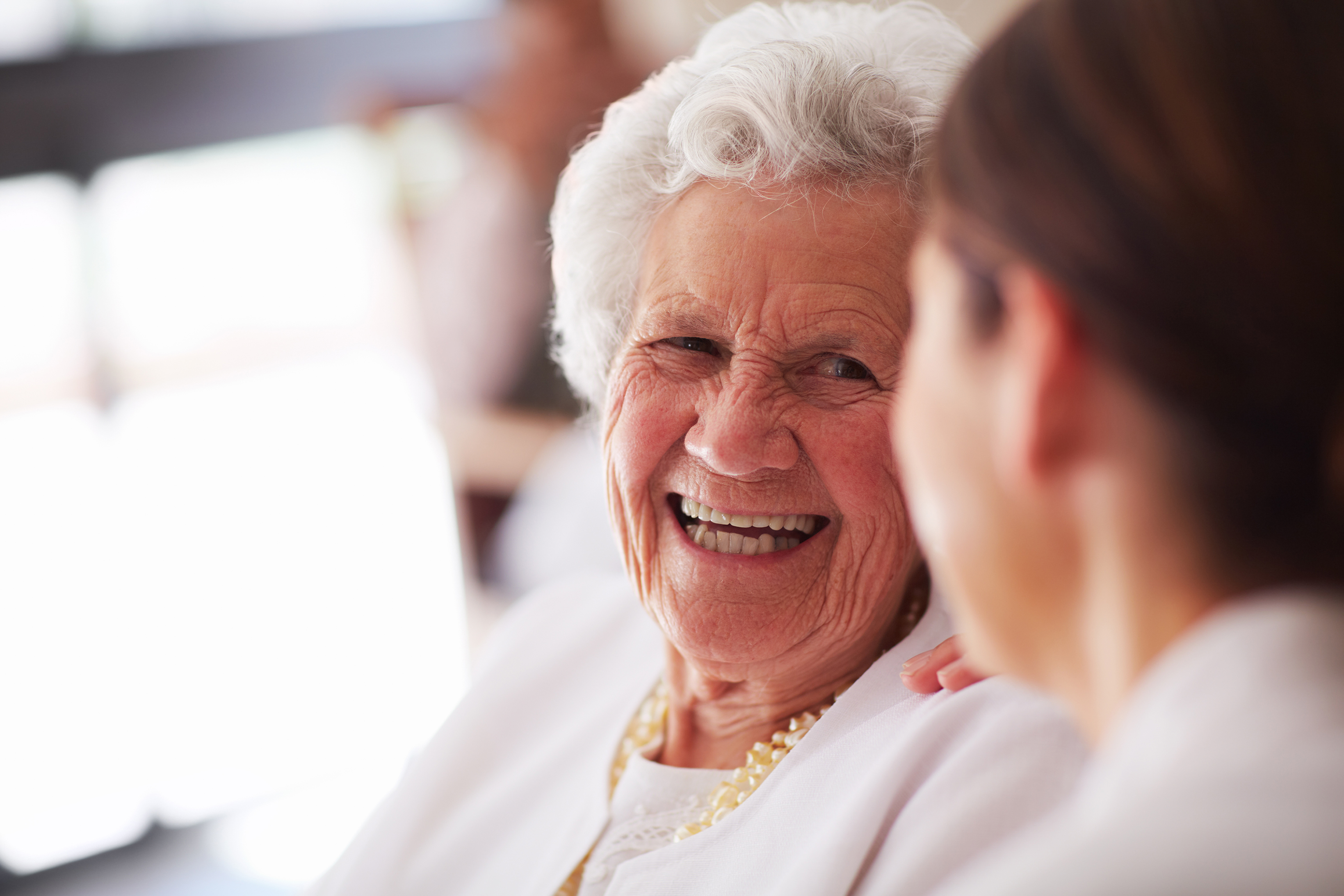 Smiling elderly woman and female nurse